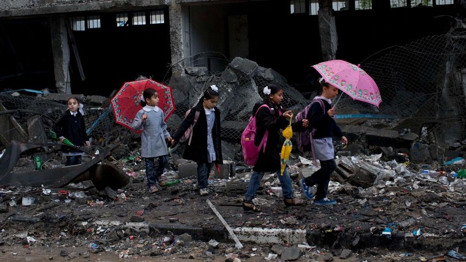Palestinian schoolchildren walk in debris by a damaged school in Gaza City, Saturday, Nov. 24, 2012. (AP / Bernat Armangue)