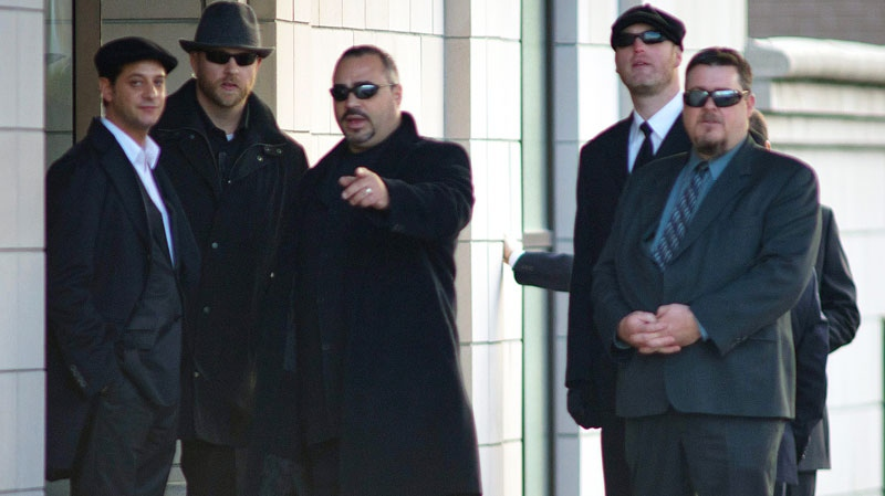 Security personnel point out a man (not shown) as he leaves the visitation for Nicolo Rizzuto at a funeral home in Montreal, Sunday, November 14, 2010. (Peter McCabe / THE CANADIAN PRESS)