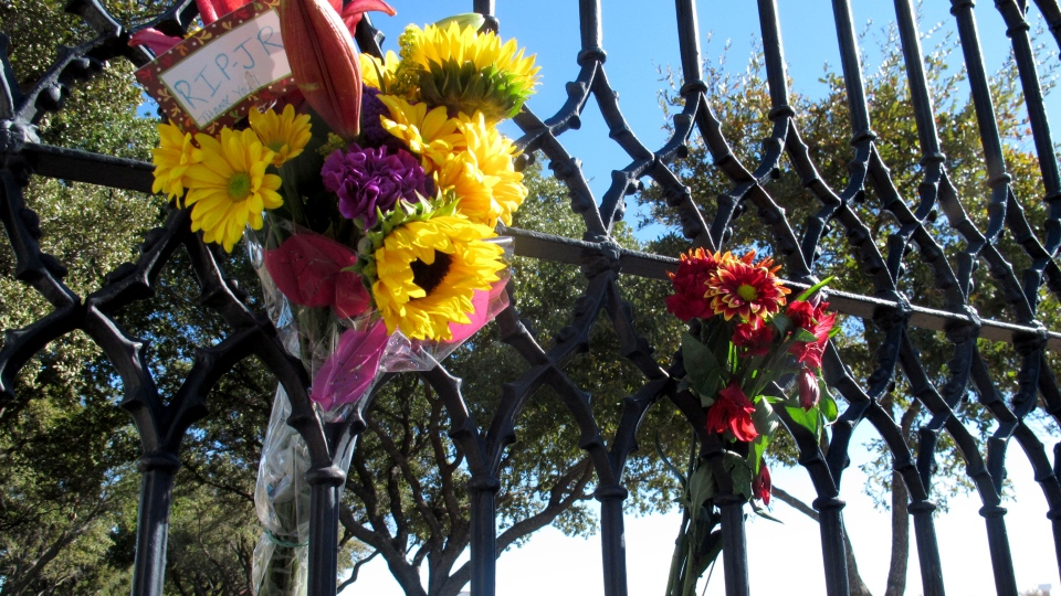 Southfork Ranch can be seen through a gate where fans left flowers in memory of Larry Hagman, in Parker, Texas, Saturday, Nov. 24, 2012. (AP / Angela K. Brown)
