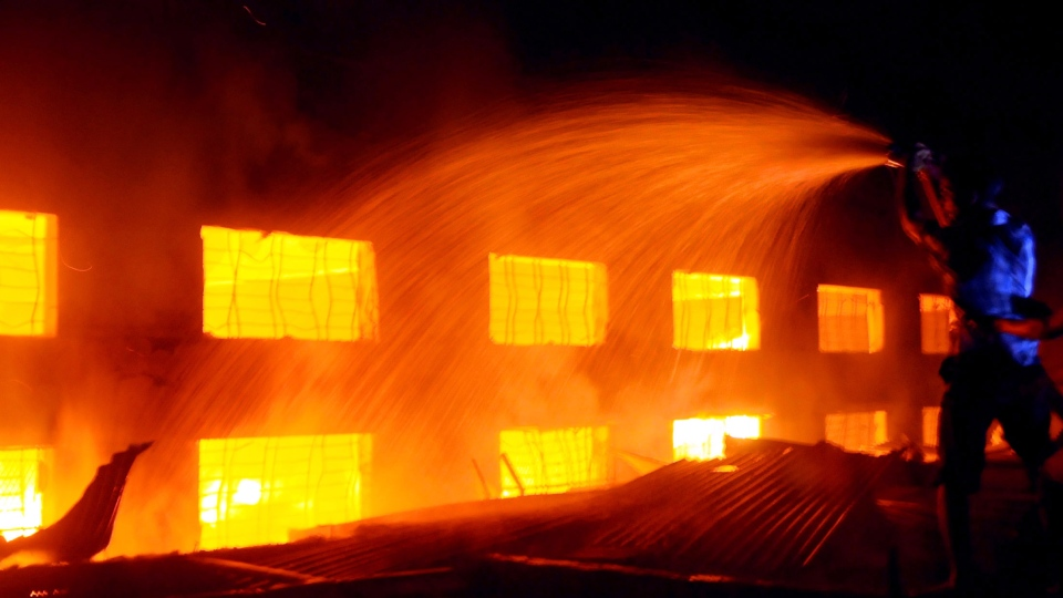 A Bangladeshi firefighter battles a fire at a garment factory ioutside Dhaka, Bangladesh on Saturday, Nov. 24, 2012.  (AP / Hasan Raza)