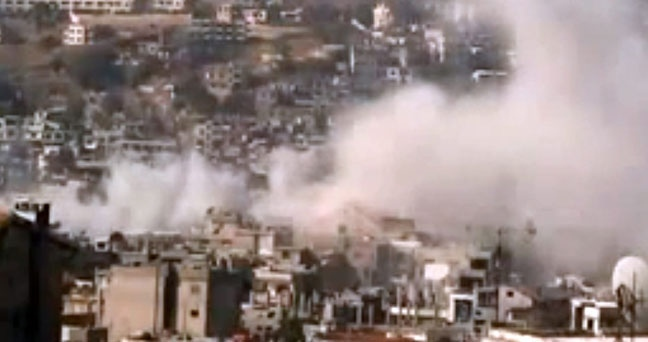 Smoke rises from buildings due to government shelling in the Damascus suburb of Zabadani, Syria, on Friday, Nov. 23, 2012. (Shaam News Network via AP video)