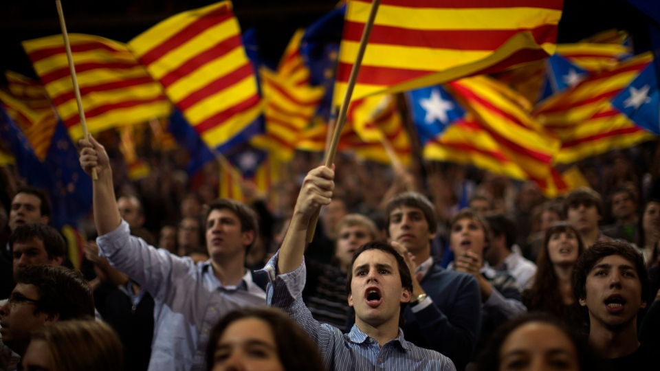"Supporters of center-right Catalan Nationalist Coalition leader, Artur Mas, wave their pro-independence ""estelada"" flags during the last day of campaigning in a meeting in Barcelona, Spain, Friday, Nov. 23, 2012.  (AP / Emilio Morenatti)"