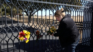 Kelli Pearson of Rowlett, attaches a bouquet of yellow roses to the front gate of Southfork Ranch, setting for TV show 'Dallas', in Parker, Texas, in memory of actor Larry Hagman Saturday, Nov. 24 2012. (AP Photo/The Dallas Morning News, Ron Baselice)