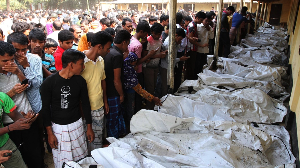 Bangladeshi people identify the bodies of their relatives killed in a fire at a garment factory in the Savar neighborhood in Dhaka, Bangladesh, Sunday, Nov. 25, 2012. (AP / Polash Khan)