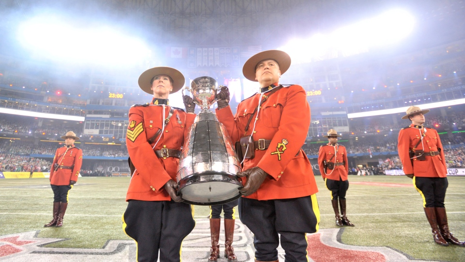 RCMP officers carry the Grey Cup during a pre-game ceremony before the 100th CFL Grey Cup between the Toronto Argonauts and the Calgary Stampeders in Toronto, on Sunday, Nov. 25, 2012. (Nathan Denette / THE CANADIAN PRESS)