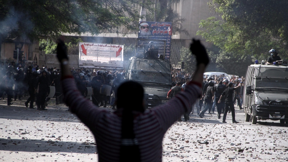 Egyptian security forces, background, clash with protesters near Tahrir Square in Cairo on Sunday, Nov. 25, 2012. Supporters and opponents of Egypt's president grow more entrenched in their potentially destabilizing battle over the Islamist leader's move to give himself near absolute powers, with neither side appearing willing to back down. (AP Photo/Ahmed Gomaa)