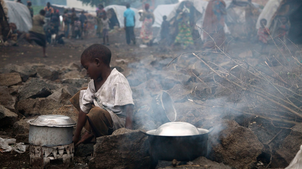 An internally displaced Congolese child heats water at the Mugunga camp outside the eastern Congolese town of Goma, Saturday Nov. 24, 2012. (AP / Jerome Delay)
