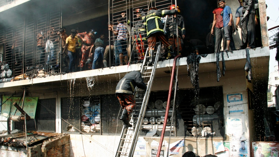 Bangladeshi firefighters and workers try to douse the fire at a garment-factory in Dhaka, Bangladesh, Monday, Nov. 26, 2012. (AP)