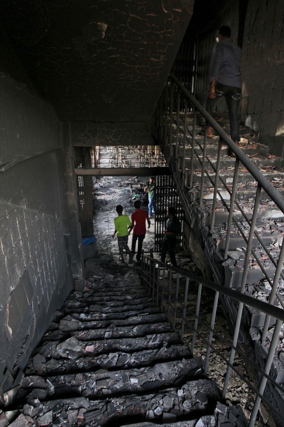 People walk inside a garment-factory where a fire killed more than 110 people Saturday on the outskirts of Dhaka, Bangladesh, Monday, Nov. 26, 2012. (AP)
