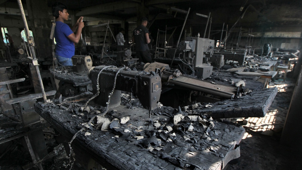 A man takes photographs inside a garment-factory where a fire killed more than 110 people Saturday on the outskirts of Dhaka, Bangladesh, Monday, Nov. 26, 2012. (AP Photo)