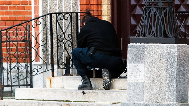 A police officer examines a suspicious package that was left on the steps of the church before a funeral service for reputed organized crime boss Nicolo Rizzuto in Montreal, Monday, Nov. 15, 2010. (Ryan Remiorz / THE CANADIAN PRESS)