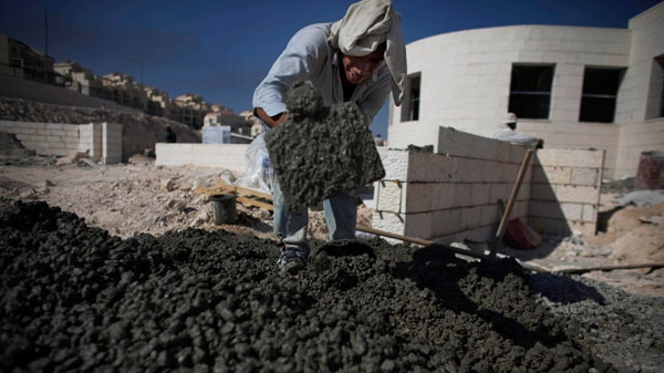 A Palestinian worker mixes cement on a construction site in the West Bank Jewish settlement of Maale Adumim, near Jerusalem, Sunday, Nov. 14, 2010. (AP / Tara Todras-Whitehill)
