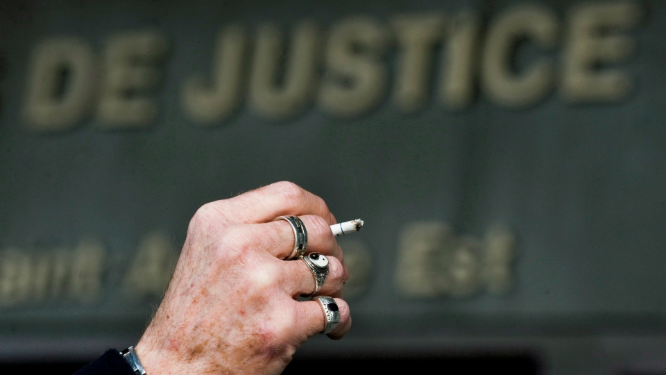 A man smokes a cigarette outside the Montreal courthouse, Monday, March 12, 2012 on the opening day of a massive lawsuit against the tobacco industry. (Graham Hughes / THE CANADIAN PRESS)