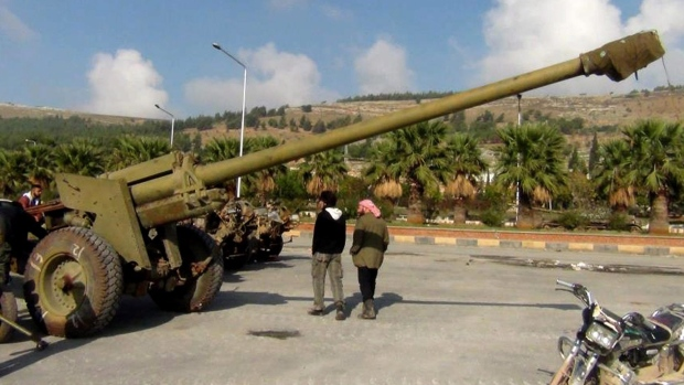 Syrian rebels walk next to a cannon