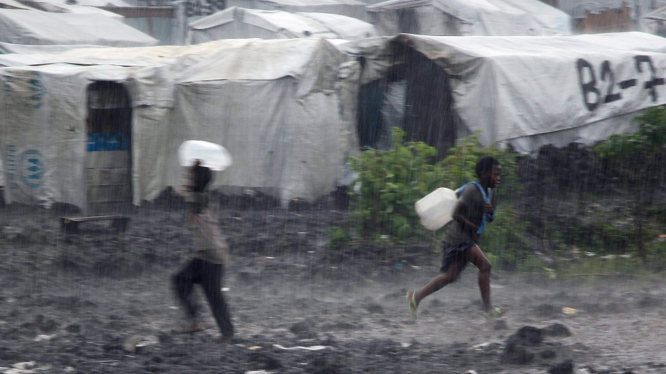Children carrying water buckets run through a rainstorm at the Mugunga 3 camp west of Goma, eastern Congo, Monday Nov. 26, 2012. (AP / Jerome Delay)