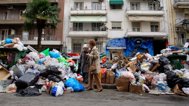 Two women pass among piles of garbage