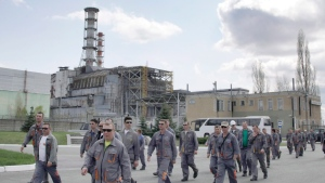 Construction workers pass by the exploded reactor at the Chernobyl nuclear power plant in Ukraine in this April 2012 file photo. (AP Photo/Efrem Lukatsky)