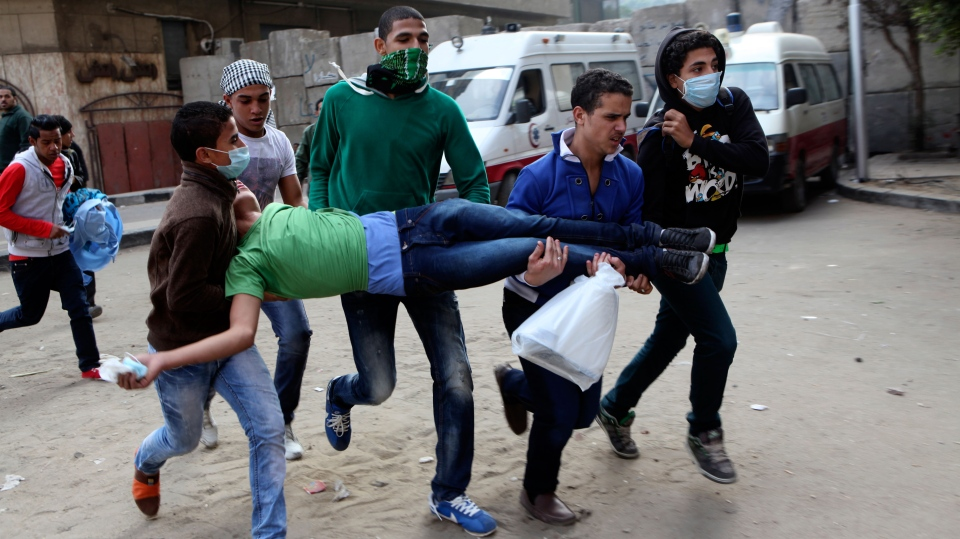 Egyptians carry a protester wounded in clashes with security forces near Tahrir square, where an opposition rally has been called for to voice rejection of President Morsi's seizure of near absolute powers, in Cairo, Egypt, Tuesday, Nov. 27, 2012. (AP / Thomas Hartwell)