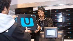 In this photo provided by Nintendo of America, a fan purchases one of the first Wii U systems in the world at the midnight launch event at Nintendo World in New York on Sunday Nov. 18, 2012. (AP Photo/Nintendo, Anders Krusberg)