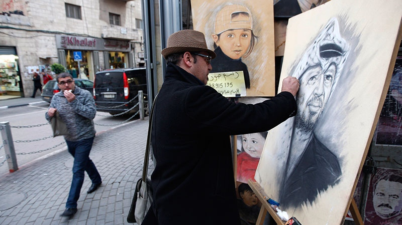 Palestinian artist Abdul Hadi paints a portrait of the late Palestinian leader, Yasser Arafat, in the West Bank city of Ramallah, Tuesday, Nov 27, 2012. (AP / Majdi Mohammed)