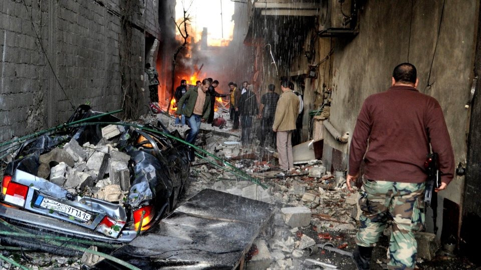 A Syrian soldier and citizens gather at an alley that was destroyed by two cars bombs, at Jaramana neighbourhood, in the suburb of Damascus, Syria, Wednesday, Nov. 28, 2012. (AP / SANA)