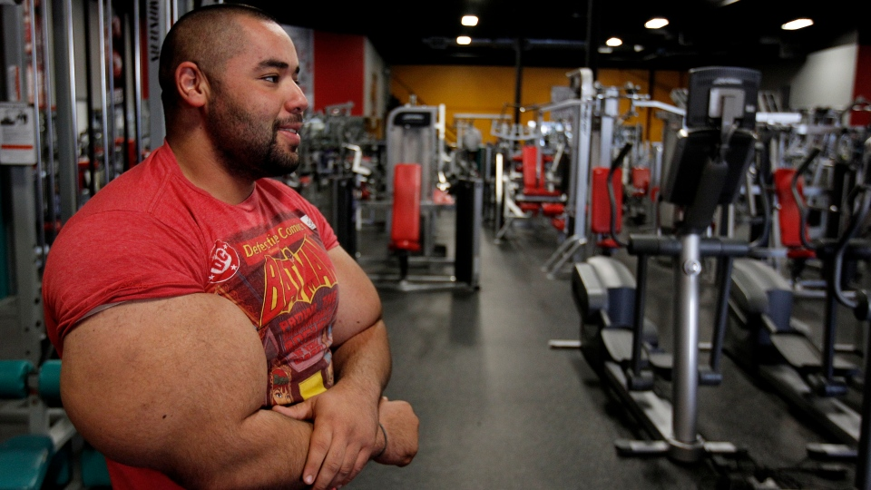 In this photo taken, Friday, Nov. 16, 2012, Egyptian Body builder Moustafa Ismail pauses before beginning another routine during his daily workout at World Gym in Milford, Mass. Ismail has been given the title of world's biggest arms, biceps and triceps, by the Guinness Book of World Records. (AP Photo/Stephan Savoia)