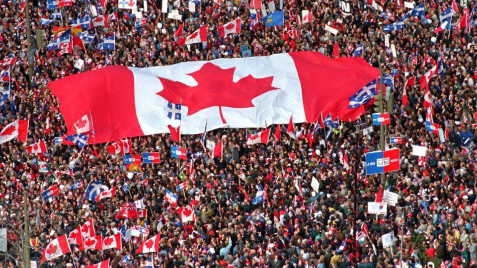 A large Canadian flag is passed through a crowd in Montreal a few days before the 1995 referendum. (Ryan Remiorz / THE CANADIAN PRESS)