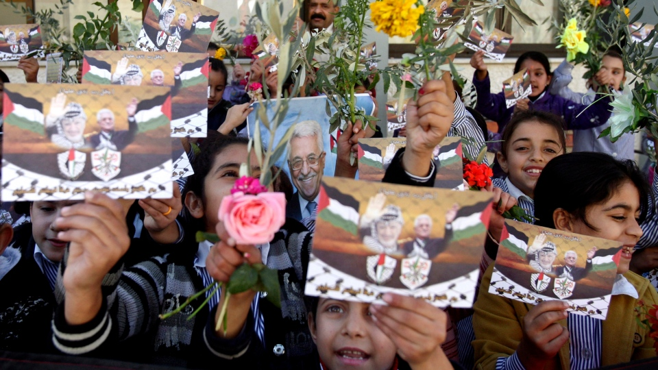 Palestinian schoolgirls hold pictures of President Mahmoud Abbas with Yasser Arafat, flowers and olive branches during a rally supporting the Palestinian UN bid for observer state status, in the West Bank city of Nablus, Wednesday, Nov. 28, 2012. (AP / Nasser Ishtayeh)