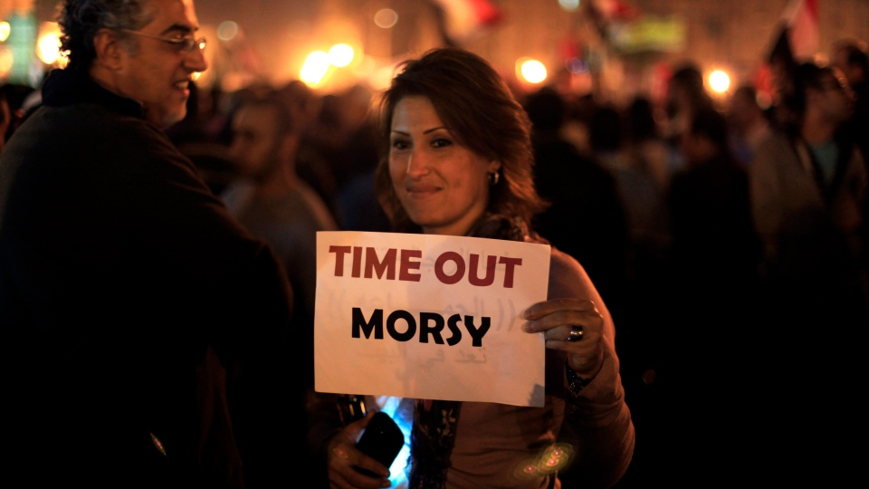 A protester holds a placard against the Egyptian president at an opposition rally in Tahrir Square in Cairo, Egypt on Tuesday, Nov. 27, 2012. (AP / Khalil Hamra)