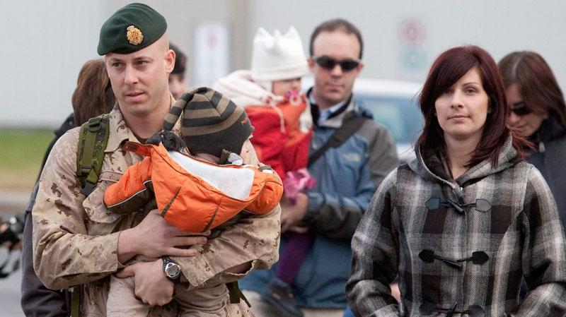 Royal 22nd Regiment Capt. Martin Rheaume carries his seven-month-old son Alexis as he and his wife Marie-Noelle Laprise, right, walk to a drill hall before leaving for Afghanistan, Monday, November 15, 2010 at CFB Valcartier Que. (Jacques Boissinot / THE CANADIAN PRESS)