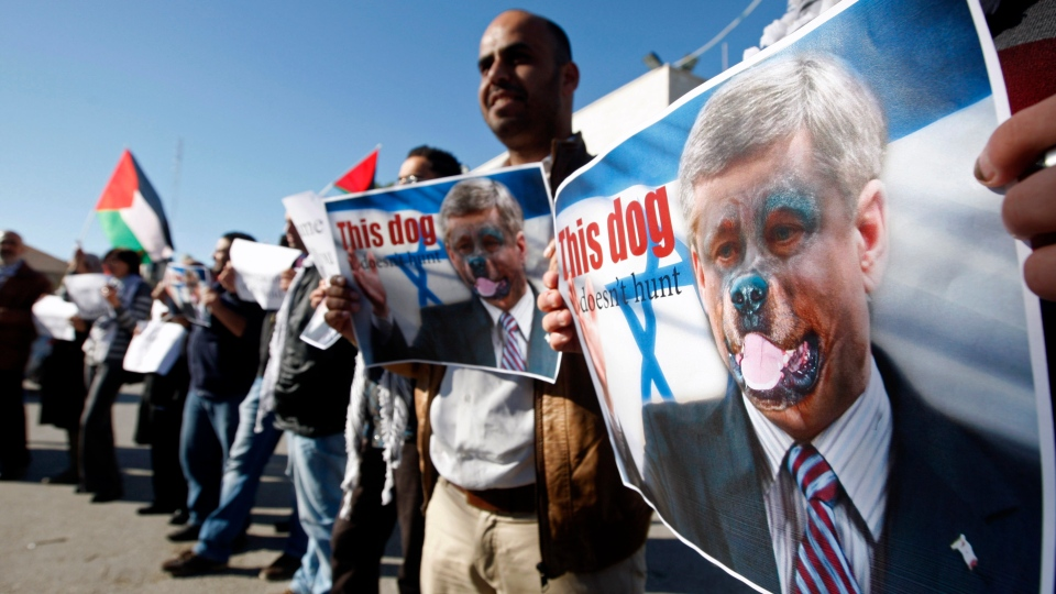 Palestinians hold pictures of Prime Minister Stephen Harper superimposed with a face of a dog during a protest following his remarks about the Palestinian UN bid for an observer state status, in front of Canadian representative offices in the West bank city of Ramallah, Wednesday, Nov. 28, 2012. (AP / Majdi Mohammed)