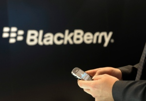 A RIM employee holds a BlackBerry device in Berlin. RIM is looking to revitalize the BlackBerry brand with the BB10. (dapd / Berthold Stadler)