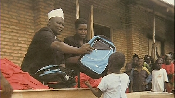 Teachers hand out school supplies to elementary students in Burundi, Africa.