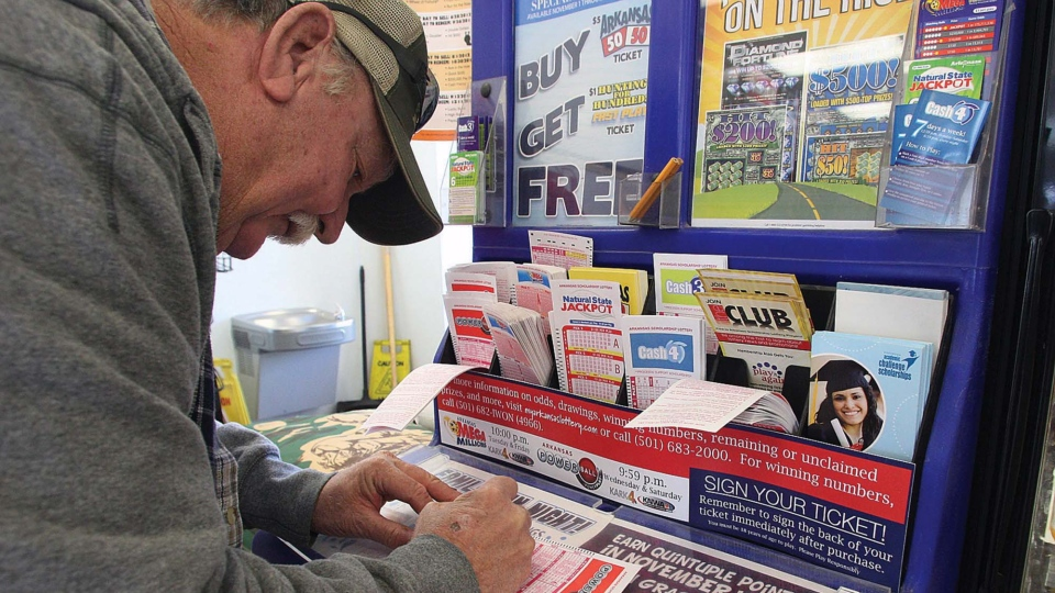 A customer at the Express Way fills in his lucky numbers for a chance to win the record setting Powerball jackpot on East Main Street in El Dorado, Ark., on Wednesday, Nov. 28, 2012. (The El Dorado News-Times, Michael Orrell)