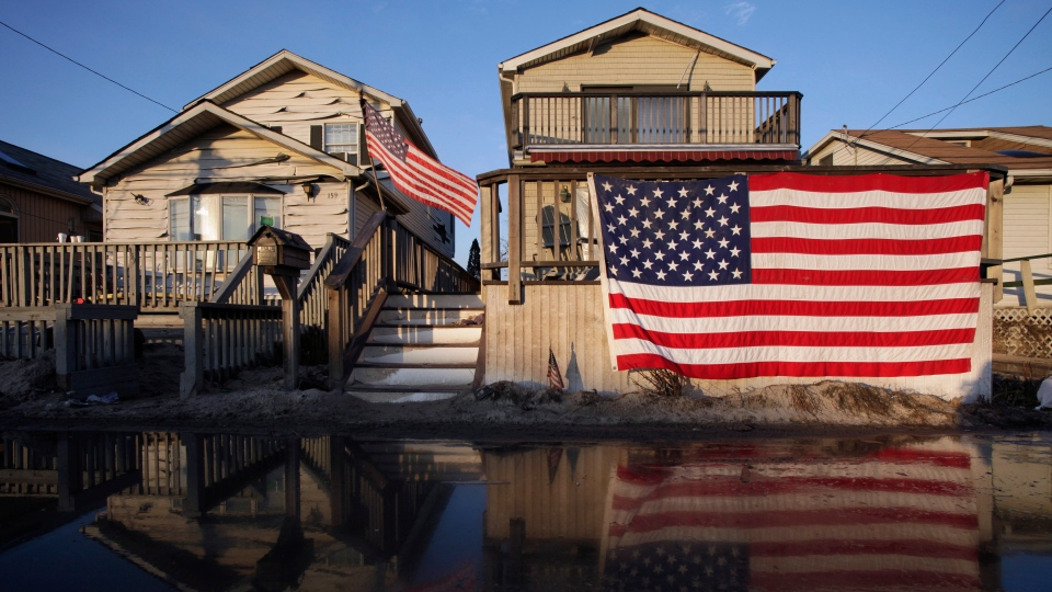 United States flags are displayed on flood-damaged homes in the Breezy Point section of Queens, N.Y., Wednesday, Nov. 28, 2012. (AP / Mark Lennihan)