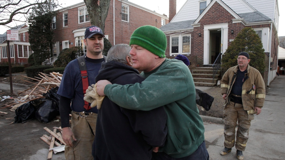 New York firefighter John Dwyer hugs New Orleans firefighter Robert Tourres, after a group of New Orleans firemen assisted in the cleanup of the Dwyer family home, flooded in Superstorm Sandy, in Queens, N.Y., Wednesday, Nov. 28, 2012. (AP / Mark Lennihan)
