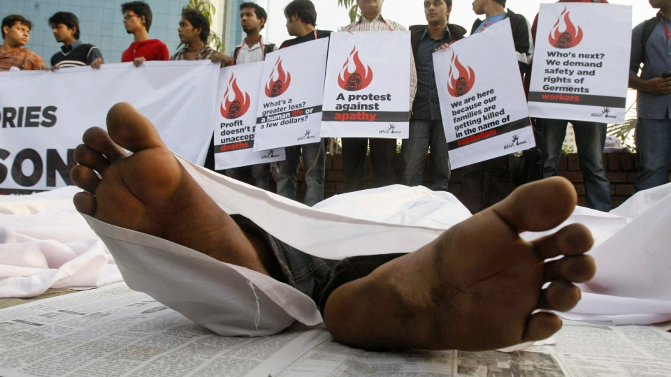 Bangladeshi protesters hold placards as some of them lie down on the ground posing as dead bodies as they condemn the death of workers in a weekend fire at a garment factory in Dhaka, Bangladesh on Wednesday, Nov. 29, 2012. (AP / Pavel Rahman)