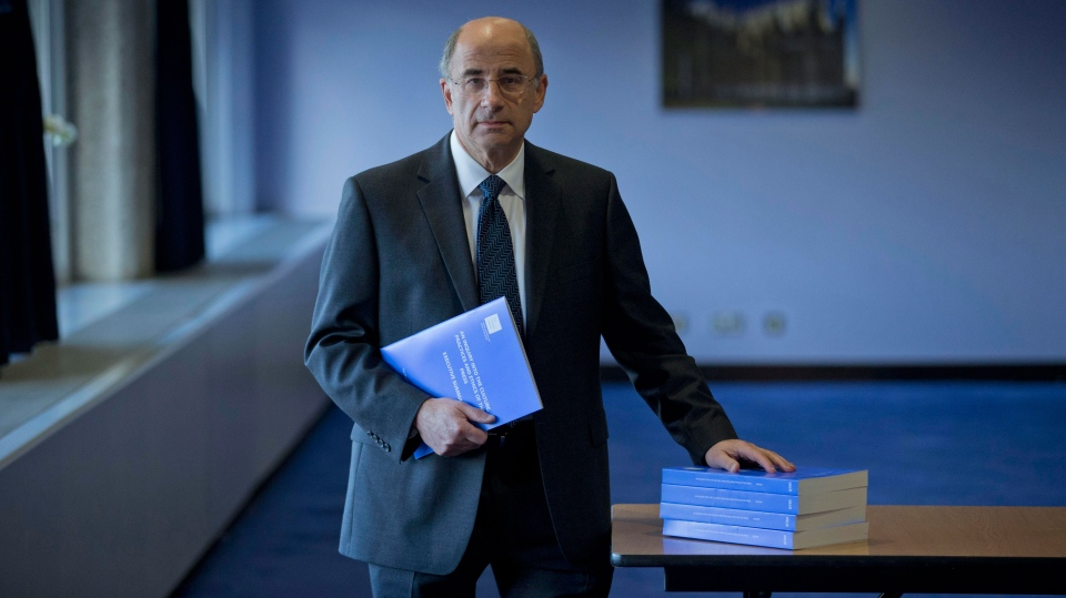Britain's Lord Justice Brian Leveson holds a summary as his hand rests on the volumes that make up his report whilst posing for photographers before the release of his report at the Queen Elizabeth II Conference Centre in London, Thursday, Nov. 29, 2012. (AP / Matt Dunham)