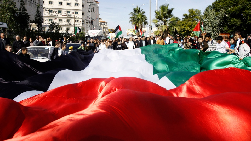 People hold a giant Palestinian flag during a rally in support of the Palestinian UN bid for observer state status, in the West Bank town of Jenin, Thursday, Nov. 29, 2012. (AP / Mohammed Ballas)
