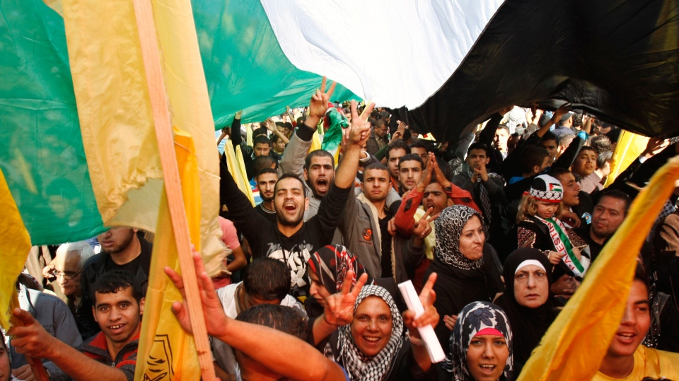 Palestinians wave Fatah and Palestinian flags during a rally in support of the Palestinian UN bid for observer state status, in Gaza City, Thursday, Nov. 29, 2012. (AP / Adel Hana)