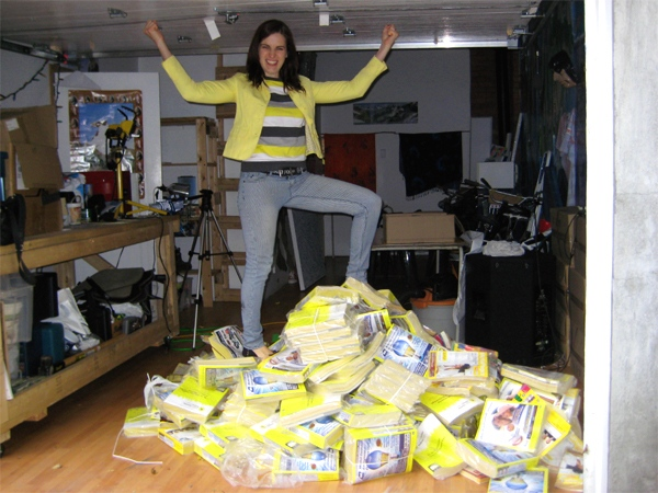 Aimee Davison standing on top of a stack of Yellow Pages directories. (Courtesy Kyle MacDonald)