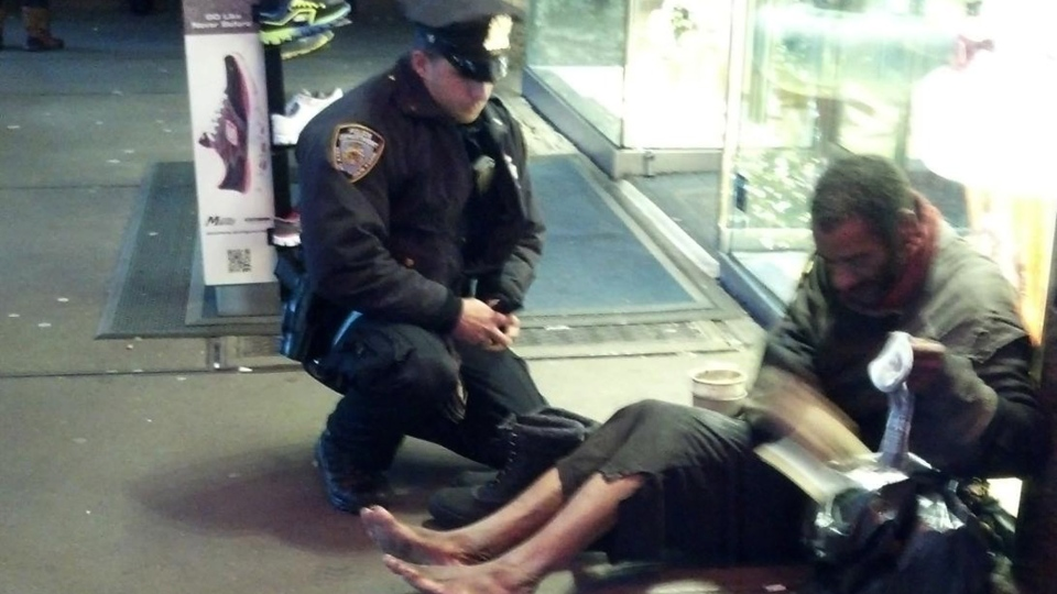"This photo provided by Jennifer Foster shows New York City Police Officer Larry DePrimo presenting a barefoot homeless man in New York's Time Square with boots Nov. 14, 2012 . The photo was posted Tuesday night to the NYPD's official Facebook page and became an instant hit. More than 350,000 users ""liked"" it as of Thursday afternoon, and over 100,000 shared it. (AP / Jennifer Foster)"