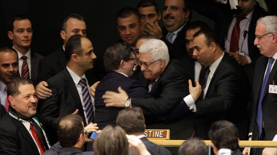 Palestinian President Mahmoud Abbas embraces a member of his delegation at the United Nations General Assembly after a vote on a resolution on the issue of upgrading the Palestinian Authority's status to non-member observer state in the United Nations in New York, Thursday, Nov. 29, 2012. (AP / Kathy Willens)