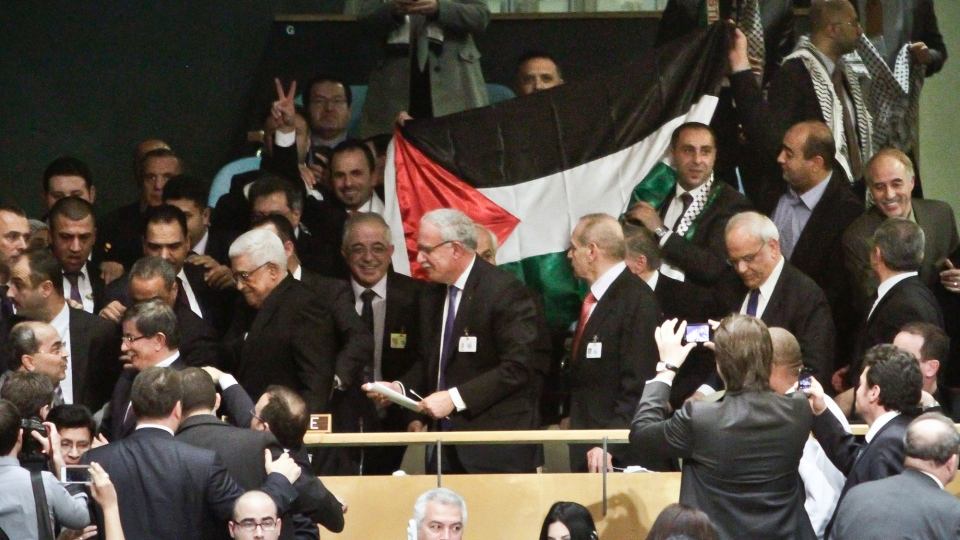 A Palestinian flag is displayed as Palestinian President Mahmoud Abbas leads his delegation from the U.N. General Assembly after a vote recognizing Palestine as a state in New York on Thursday, Nov. 29, 2012. (AP / Bebeto Matthews)