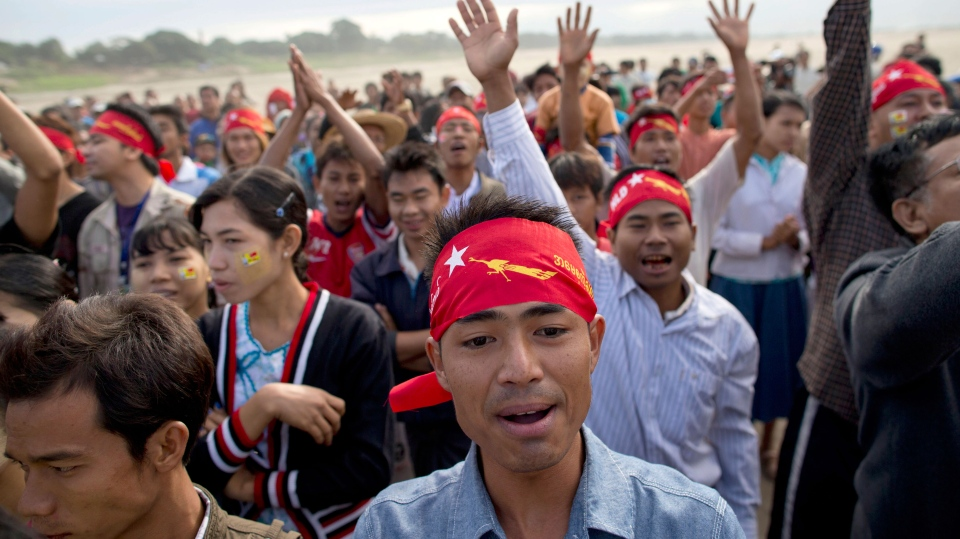Supporters of opposition leader Aung San Suu Kyi applaud as she appears to address a public meeting in a nearby village close to Letpadaung mine in Monywa, northwestern Myanmar, Friday, Nov. 30, 2012. (AP Photo/Gemunu Amarasinghe)