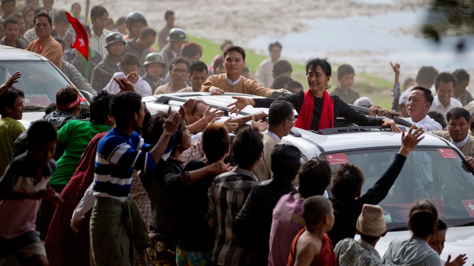 Supporters of opposition leader Aung San Suu Kyi reach to touch her hand as she leaves after a public meeting close to Letpadaung mine in Monywa, northwestern Myanmar, Friday, Nov. 30, 2012. (AP / Gemunu Amarasinghe)