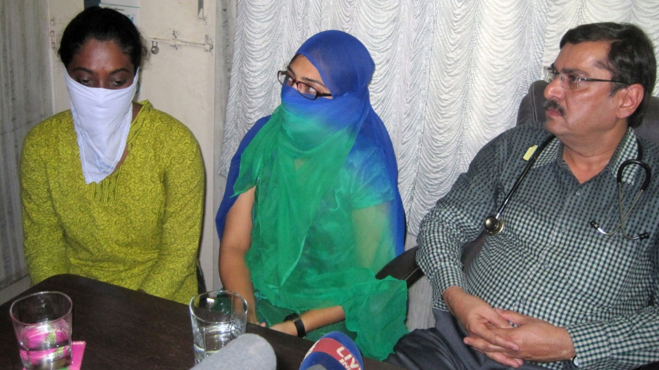 Indian women arrested for their Facebook posts, Shaheen Dhada, center, and Renu Srinivas, both faces covered, speak to the media next to Shaheen's uncle Abdul Gafar Dhada in Mumbai, India, Tuesday, Nov. 20, 2012. (AP)