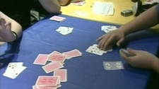 A group of young people gamble while playing card games in this undated image taken from video.