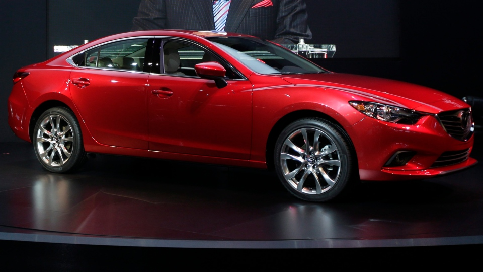 Mazda CEO Takashi Yamanouchi speaks while the Mazda6 is shown during it's North American debut at the LA Auto Show in Los Angeles, Thursday, Nov. 29, 2012. (AP Photo/Chris Carlson)