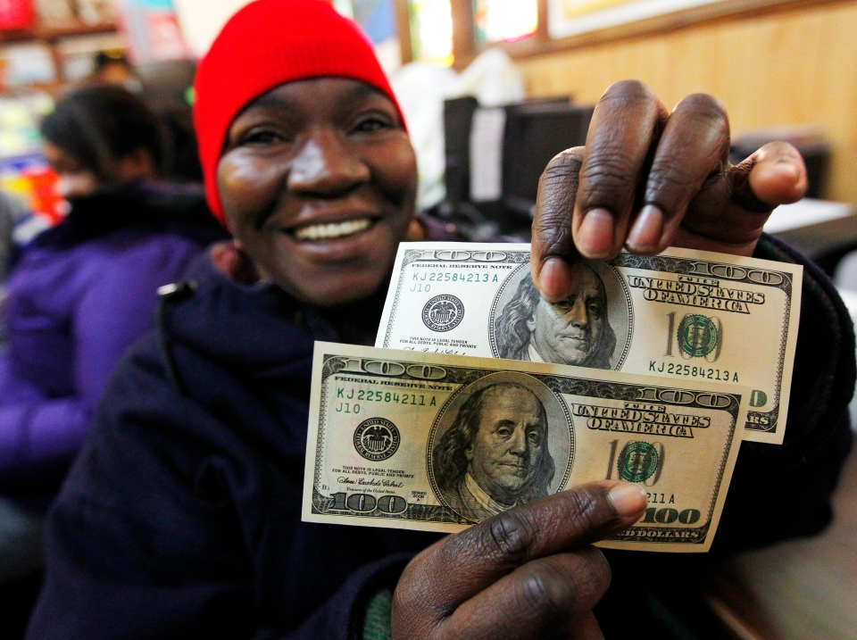 Charlotte Muhammad holds up two $100 dollar bills she got from Secret Santa, at St. Joseph's Social Service Center in Elizabeth, N.J., Thursday, Nov. 29, 2012. (AP / Rich Schultz)